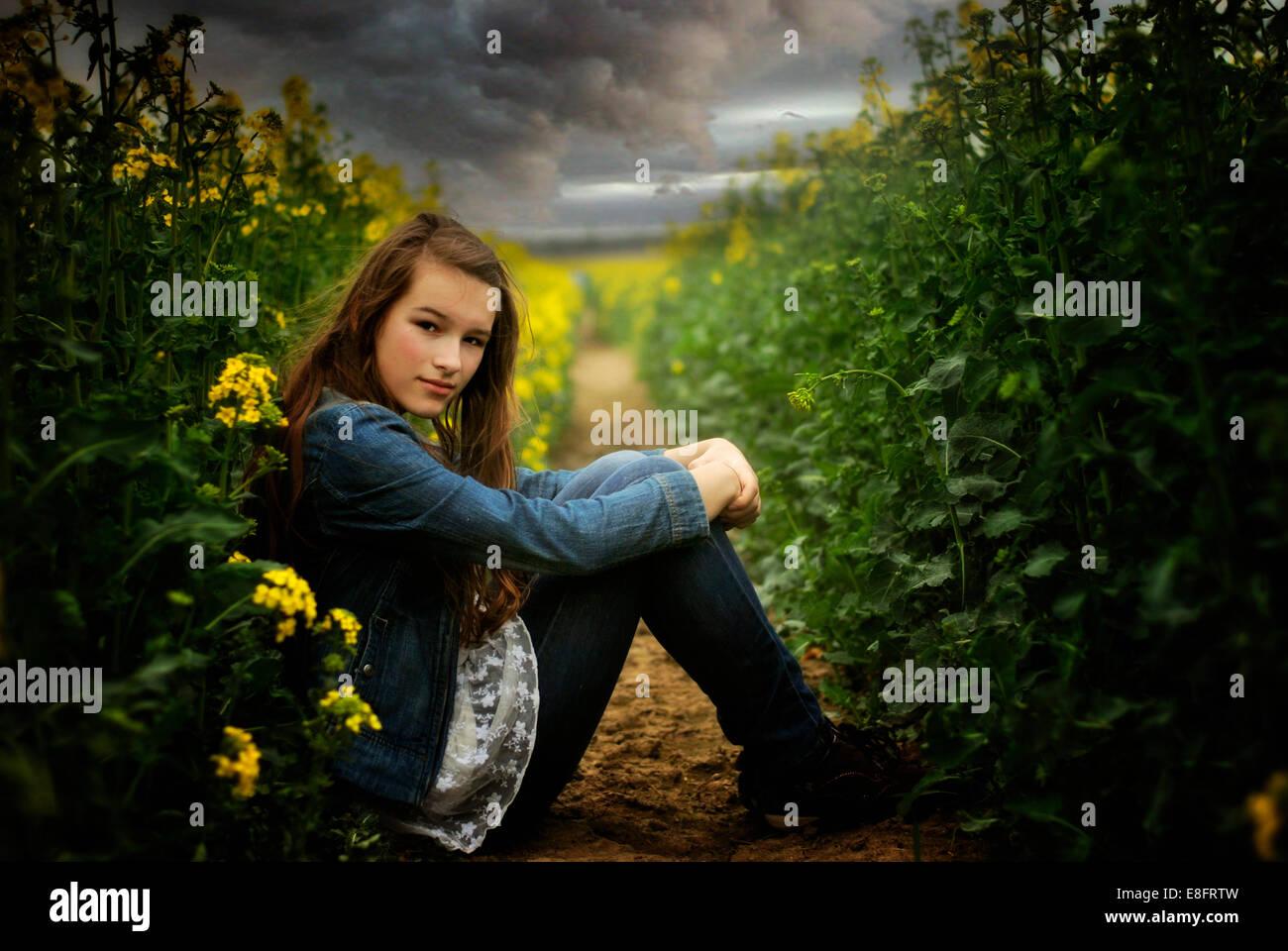 Seitenansicht der Mädchen sitzen im Feld Stockbild