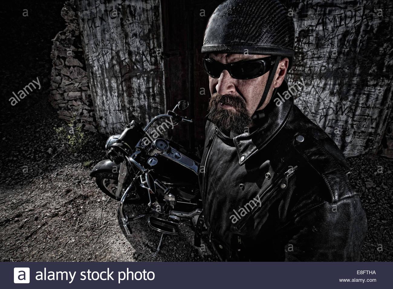 Biker mit seinem Motorrad Helm und Sonnenbrille tragen steht Stockbild