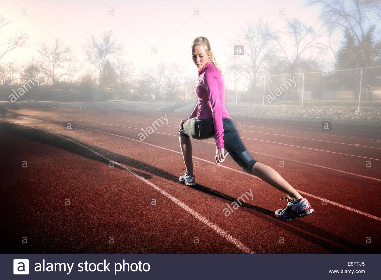 Frau auf Laufstrecke stretching und anhören von Musik, Colorado, America, USA Stockbild