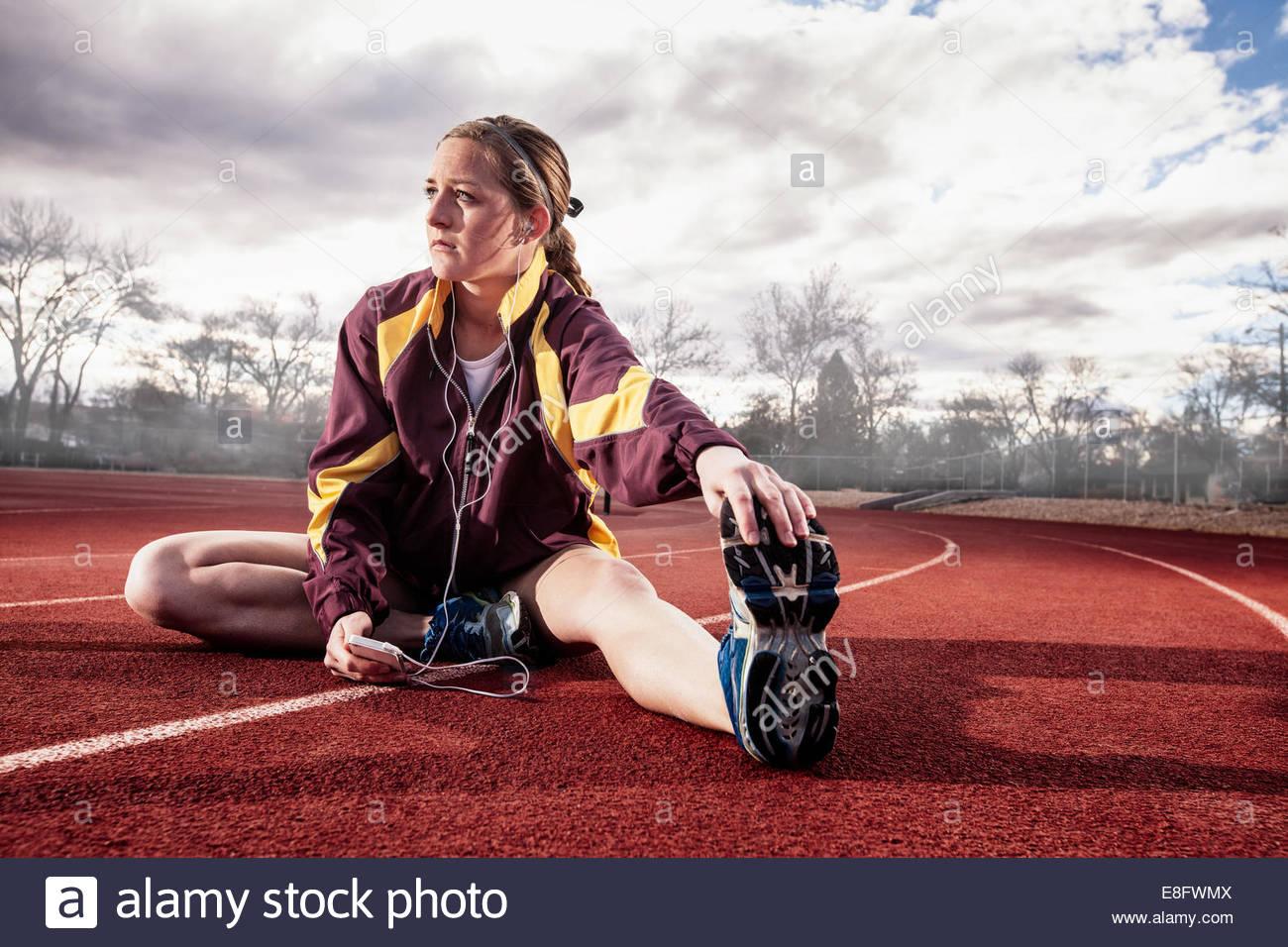 Junge Frau sitzt auf der Laufstrecke Dehnung beim Musikhören Stockbild