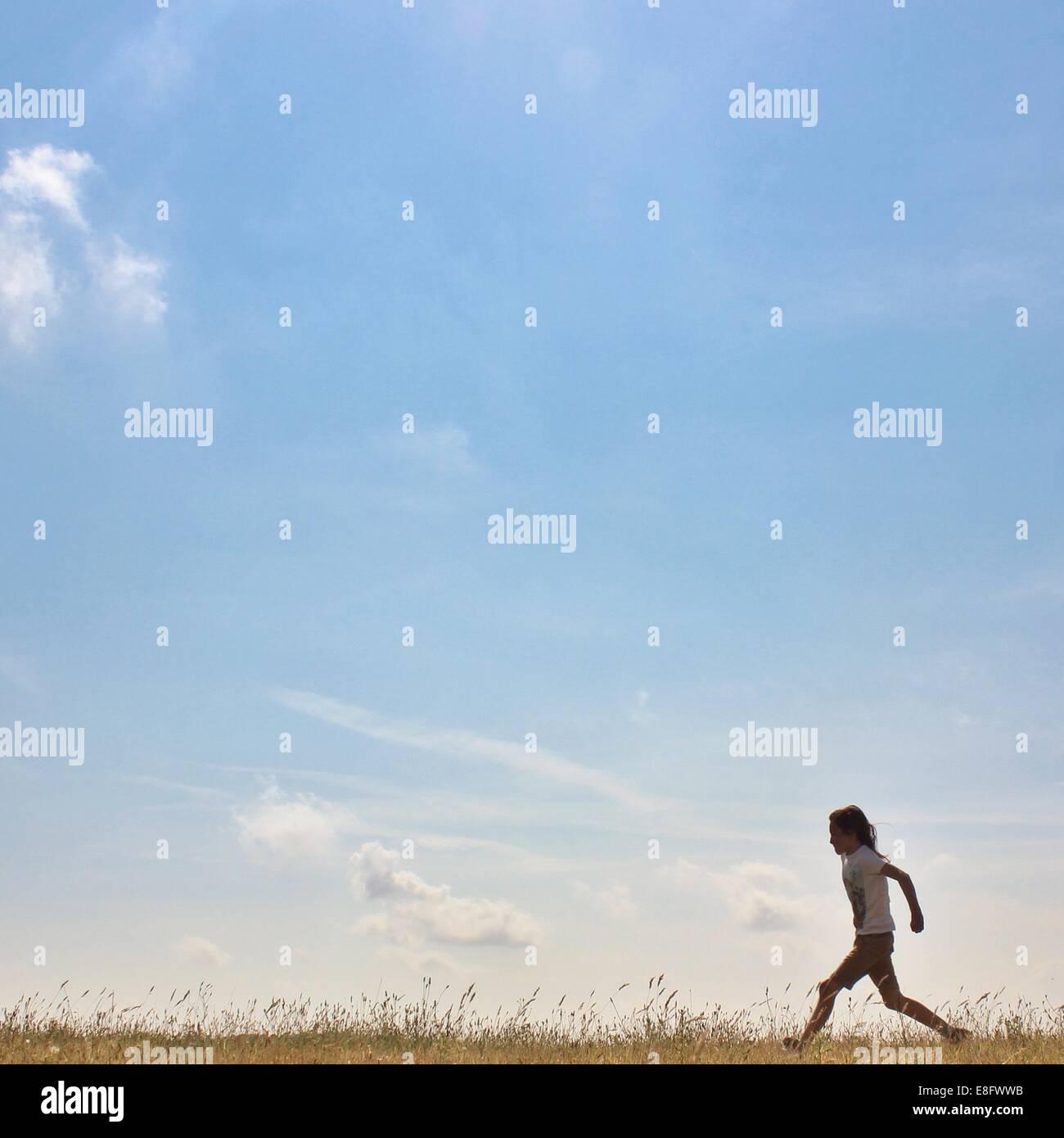 Seitenansicht eines Mädchens im ländlichen Landschaft laufen Stockbild