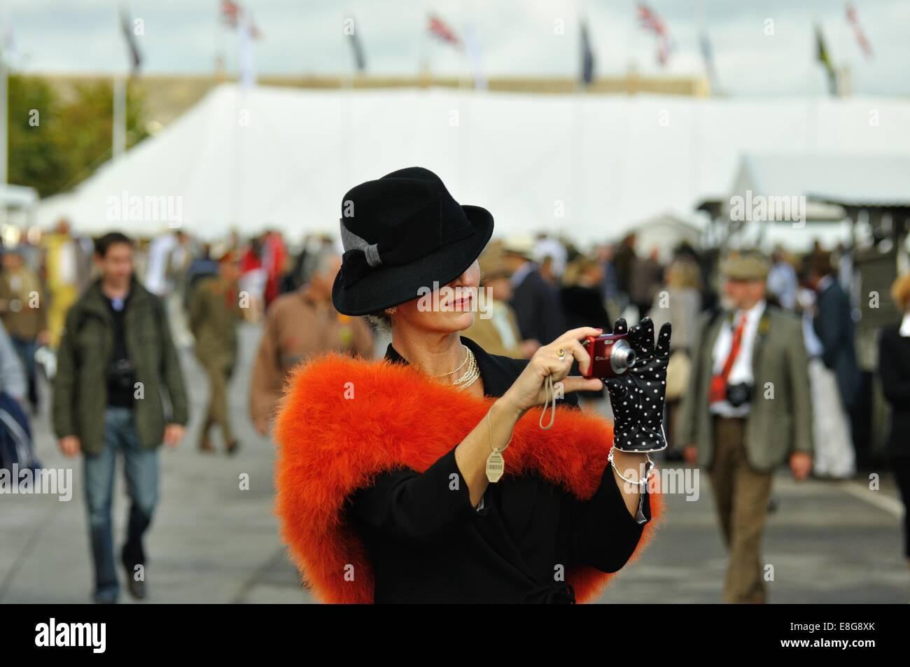 Lady trägt Vintage Mode eine Aufnahme mit einer Kompaktkamera beim Goodwood Revival Stockbild