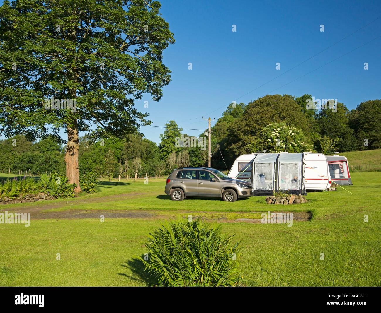 Preiswerte camping-Platz mit Wohnwagen mit Anbau eingerichtet neben Auto / SUV im Feld mit Rasen & Schatten Stockbild