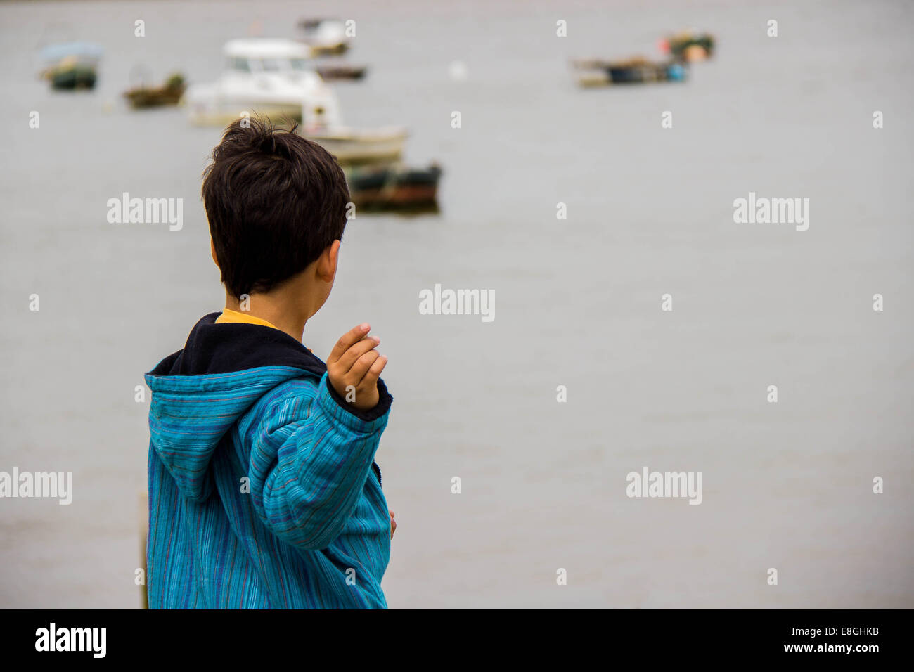 Spanien, Madrid, junge spielt mit Steinen im Meer Stockbild