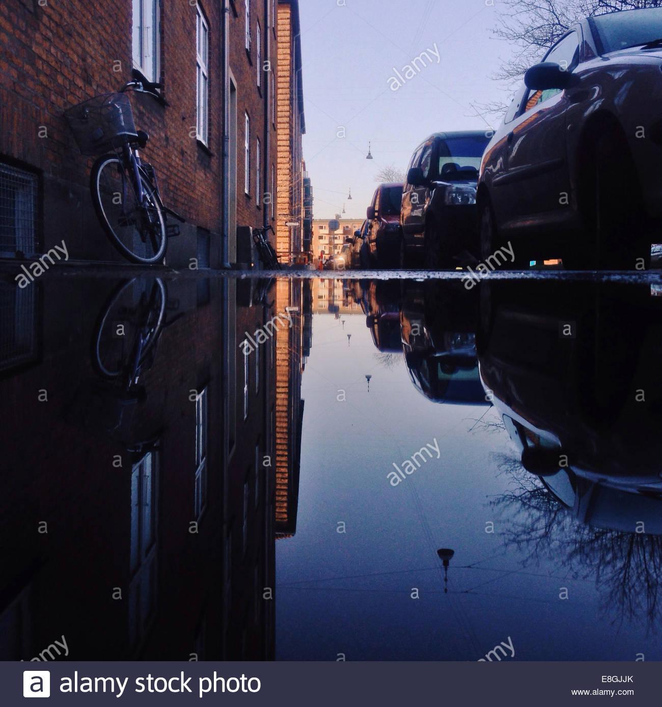 Parkende Autos spiegelt sich in der Pfütze Stockbild
