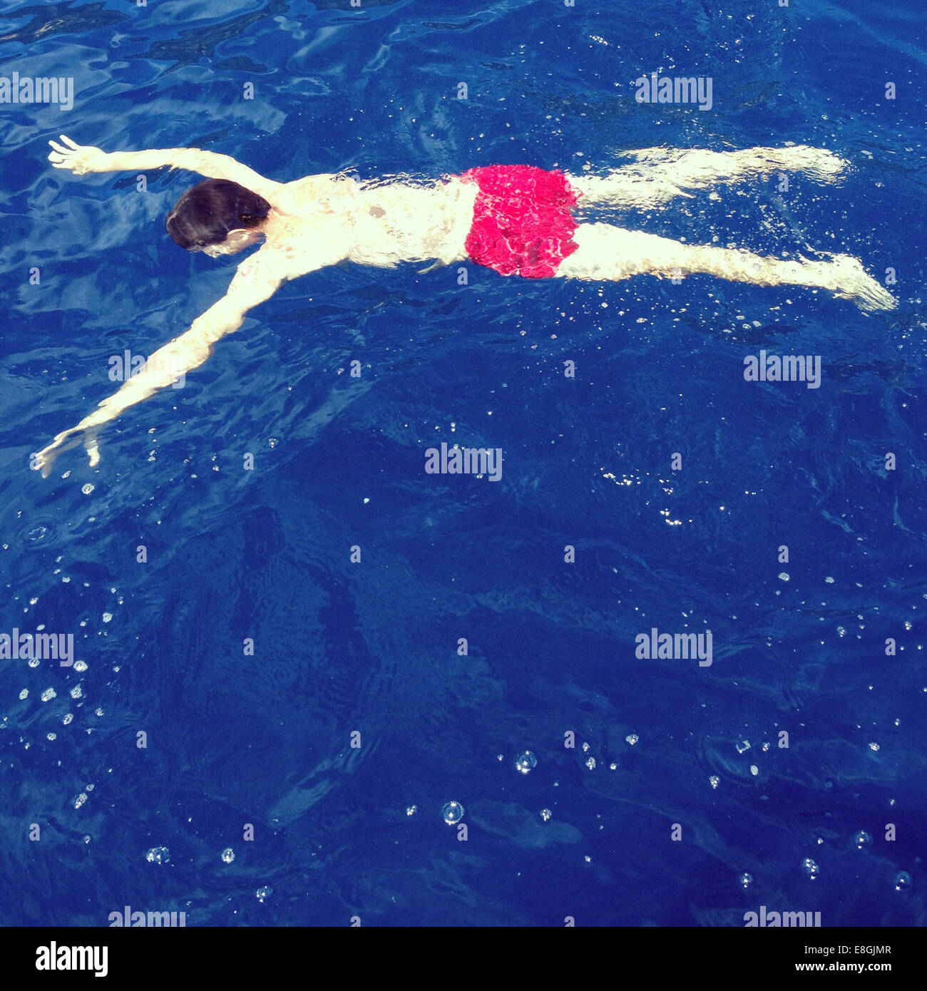 Mann, Schwimmen im Meer verdeckt Stockbild