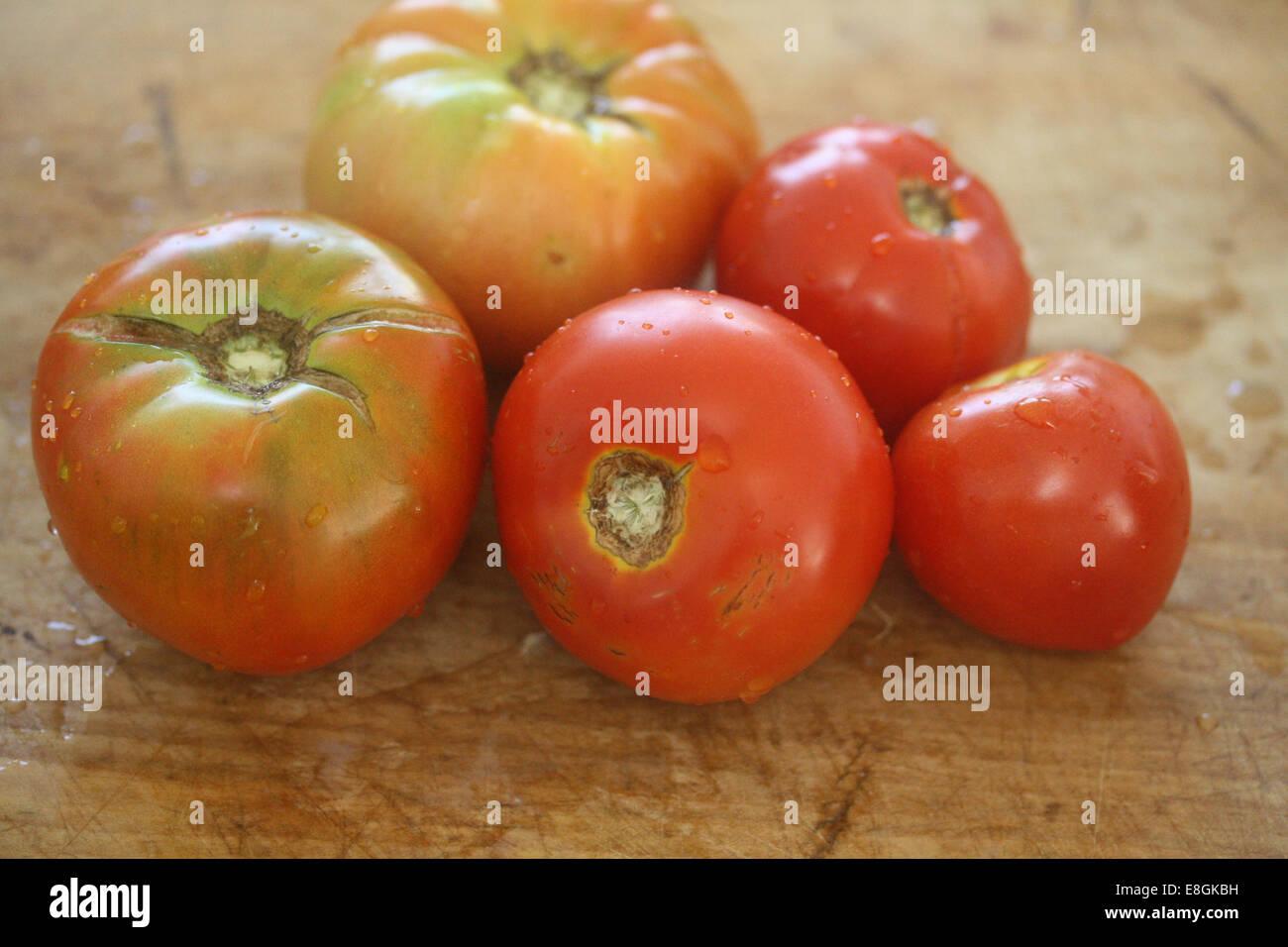 Fünf Heirloom Tomatoes auf Schneidbrett aus Holz Stockbild