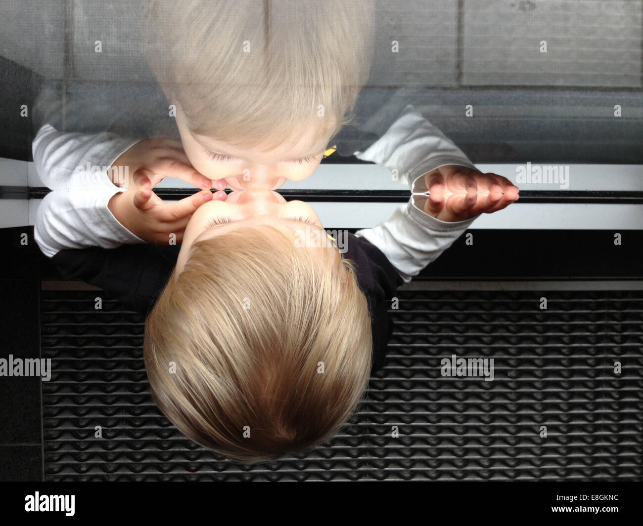 Stockholm, Schweden ein kleiner Junge, der Blick durch ein Fenster und sehen, sein eigenes Spiegelbild Stockbild