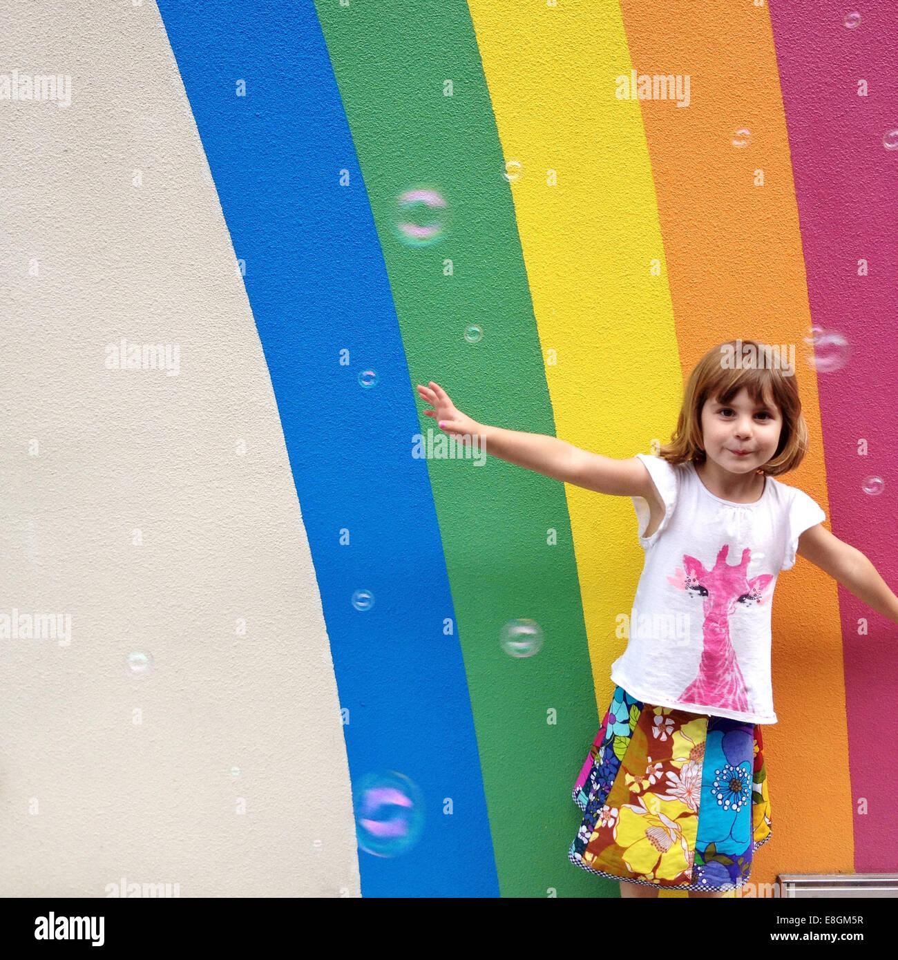 Mädchen (4-5) mit Blase vor gemalten Regenbogen tanzen Stockbild
