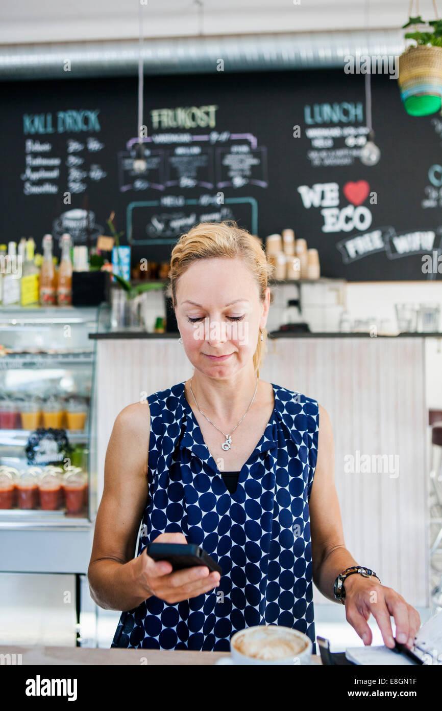 Porträt der lächelnde Frau mit Kaffee am Tisch im café Stockbild