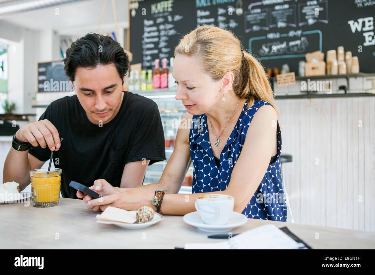 Glücklich multiethnischen Freunde mit Handy am Tisch im café Stockbild