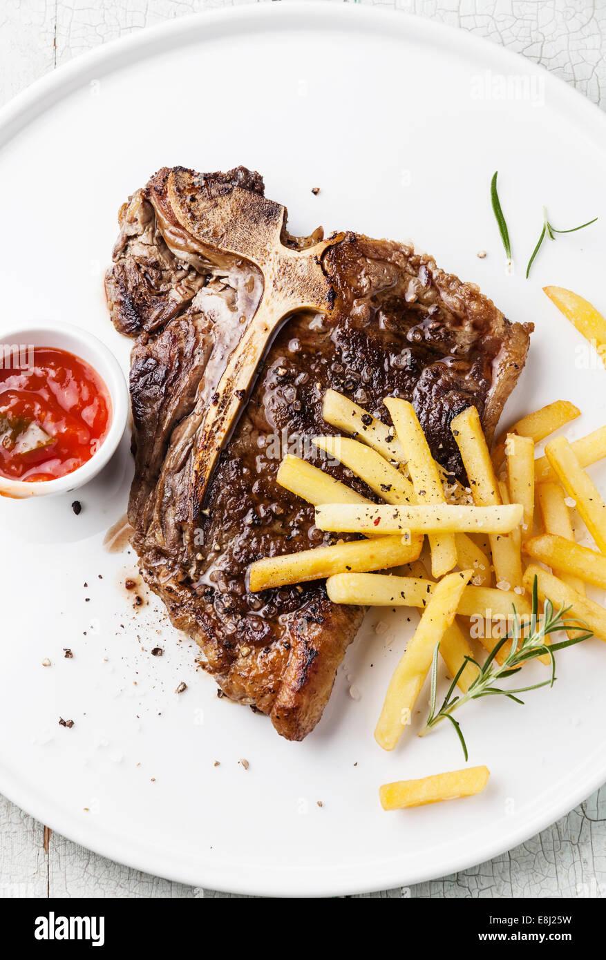 T-Bone Steak mit Pommes gesalzen auf weißen Teller auf blauem Hintergrund aus Holz Stockbild