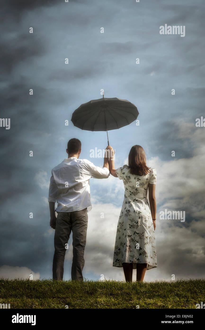 ein paar auf einer Wiese mit einem Regenschirm Stockbild