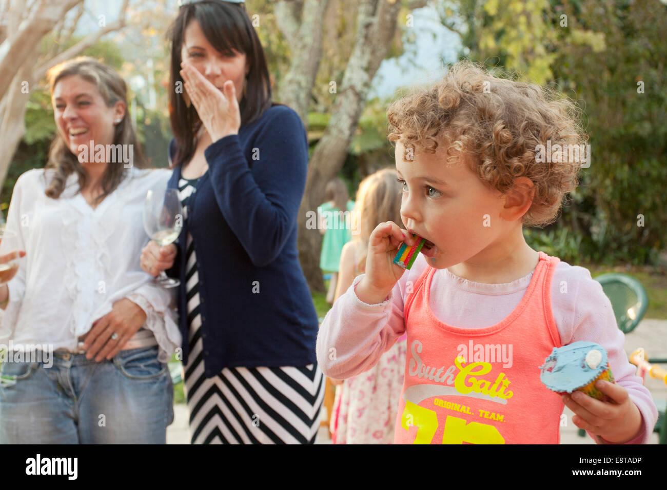 Junges Mädchen essen ihre Tasse Kuchen auf einer Party. Stockbild
