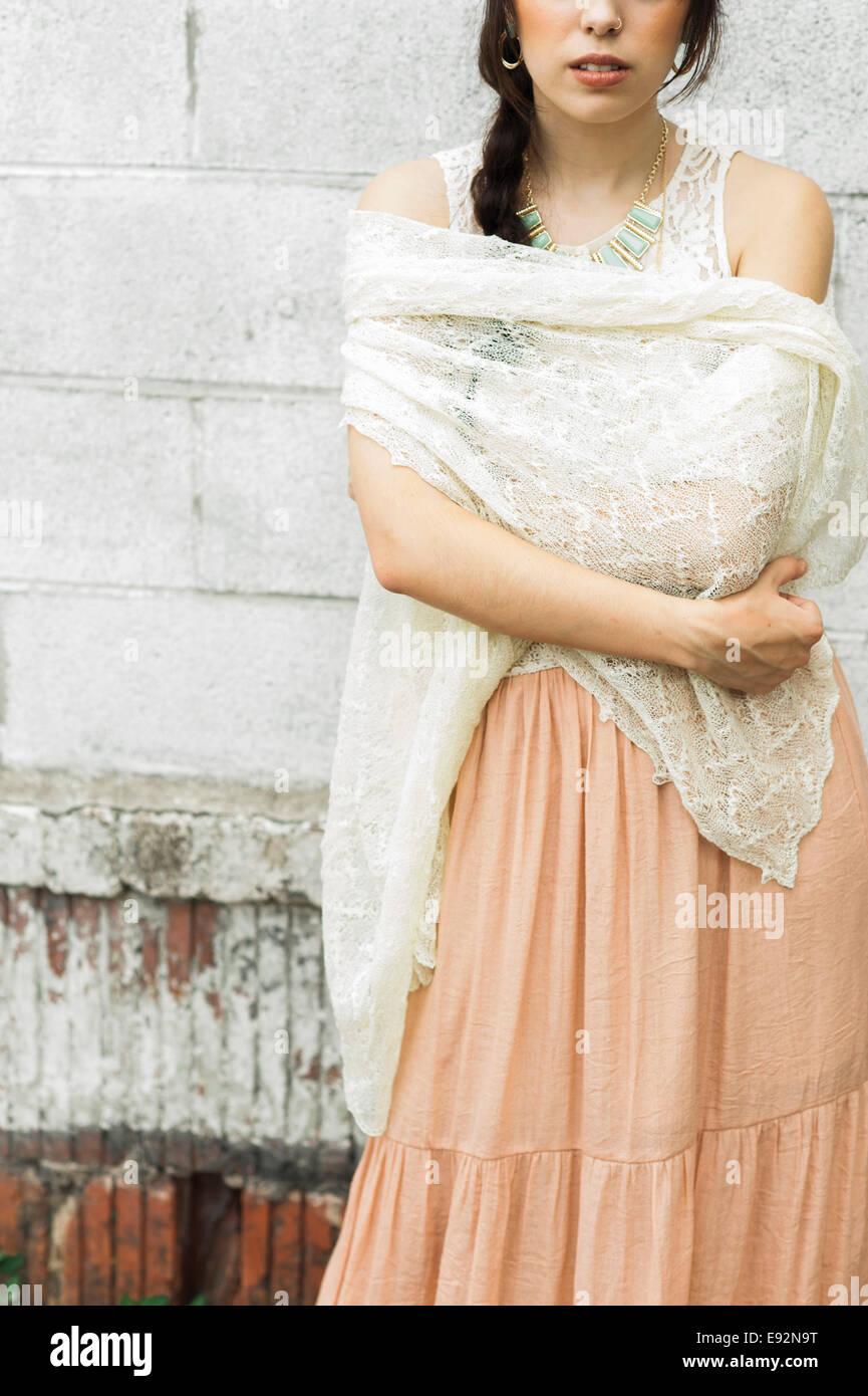 Junge Frau mit gehäkelten Schal Ziegel Hintergrund, Nahaufnahme Stockbild