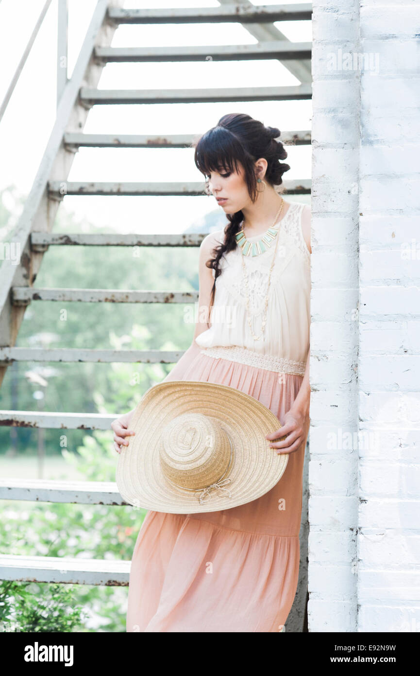 Junge Frau in rosa Rock mit Strohhut neben Feuerleiter Treppen Stockbild