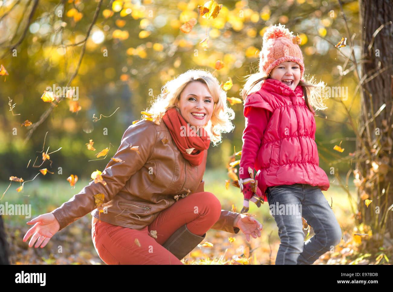 Glückliche Eltern und Kind im freien Spiel mit gelben Blätter im Herbst Stockbild