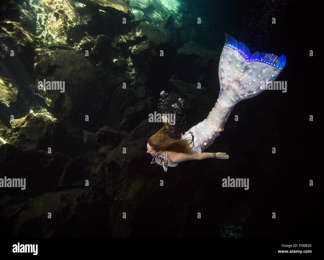 Meerjungfrau mit einem leuchtenden Schweif, Schwimmen in den Gewässern der Halbinsel Yucatan, KuKulKan Cenote, Stockbild