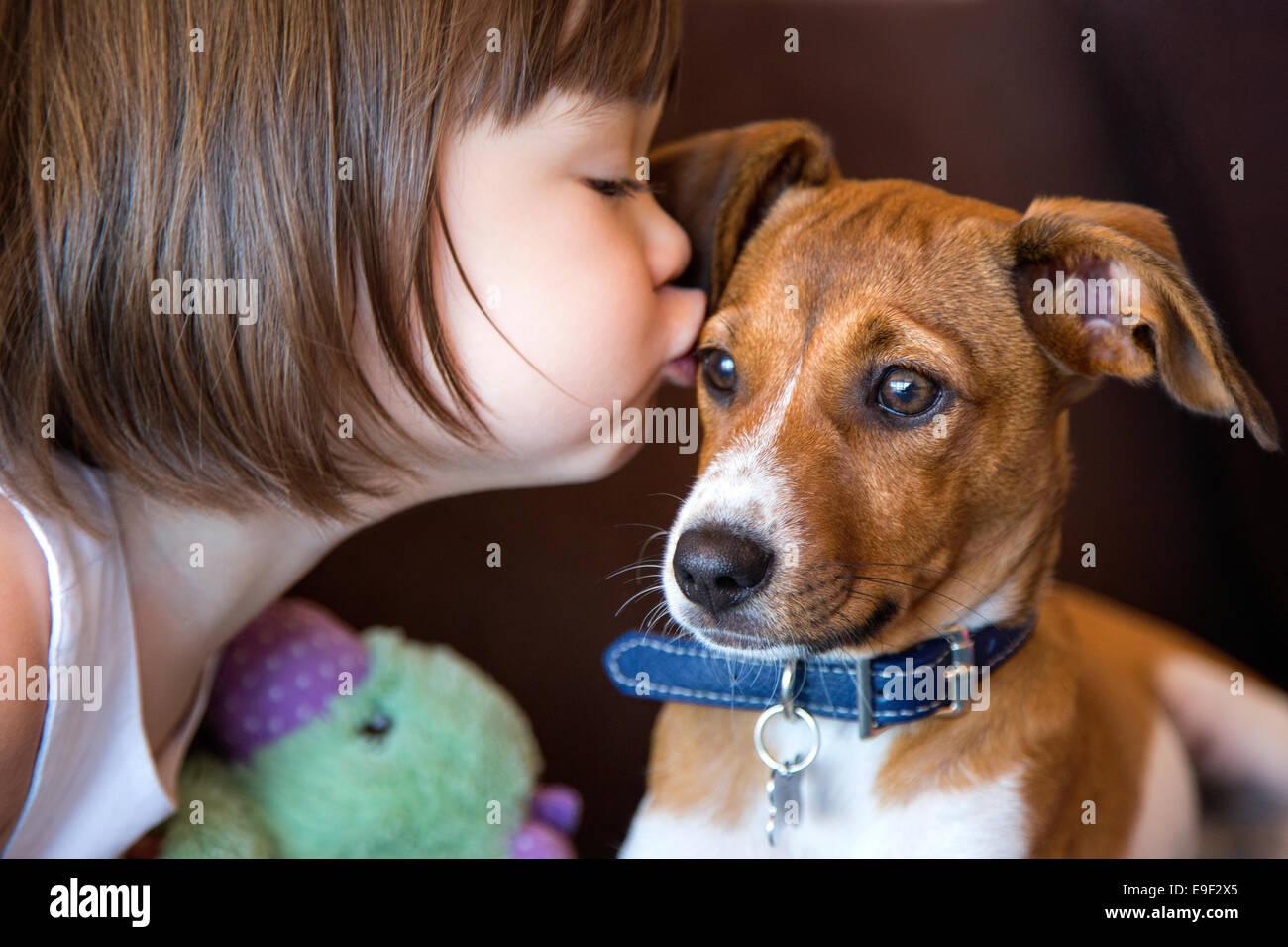Kleinkind Mädchen küssen ihr Hündchen Stockbild