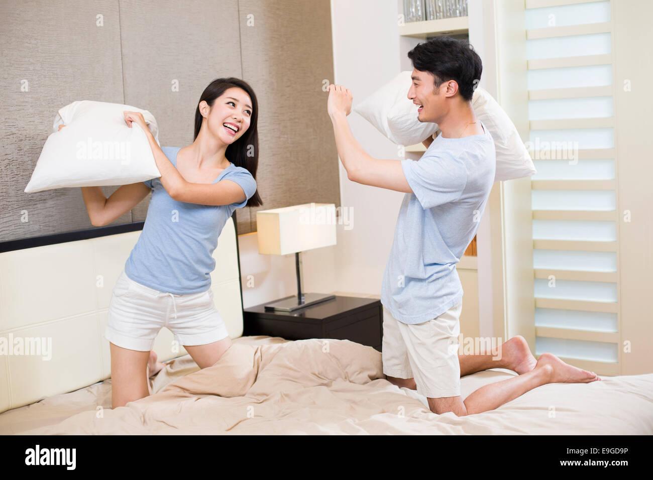 Junges Paar Kissen Kämpfe im Schlafzimmer Stockbild