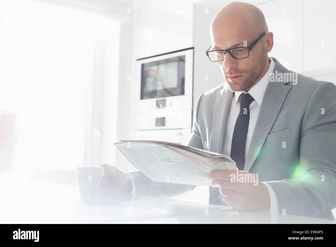 Mitte adult Geschäftsmann Kaffeetrinken beim lesen Zeitung zu Hause Stockbild