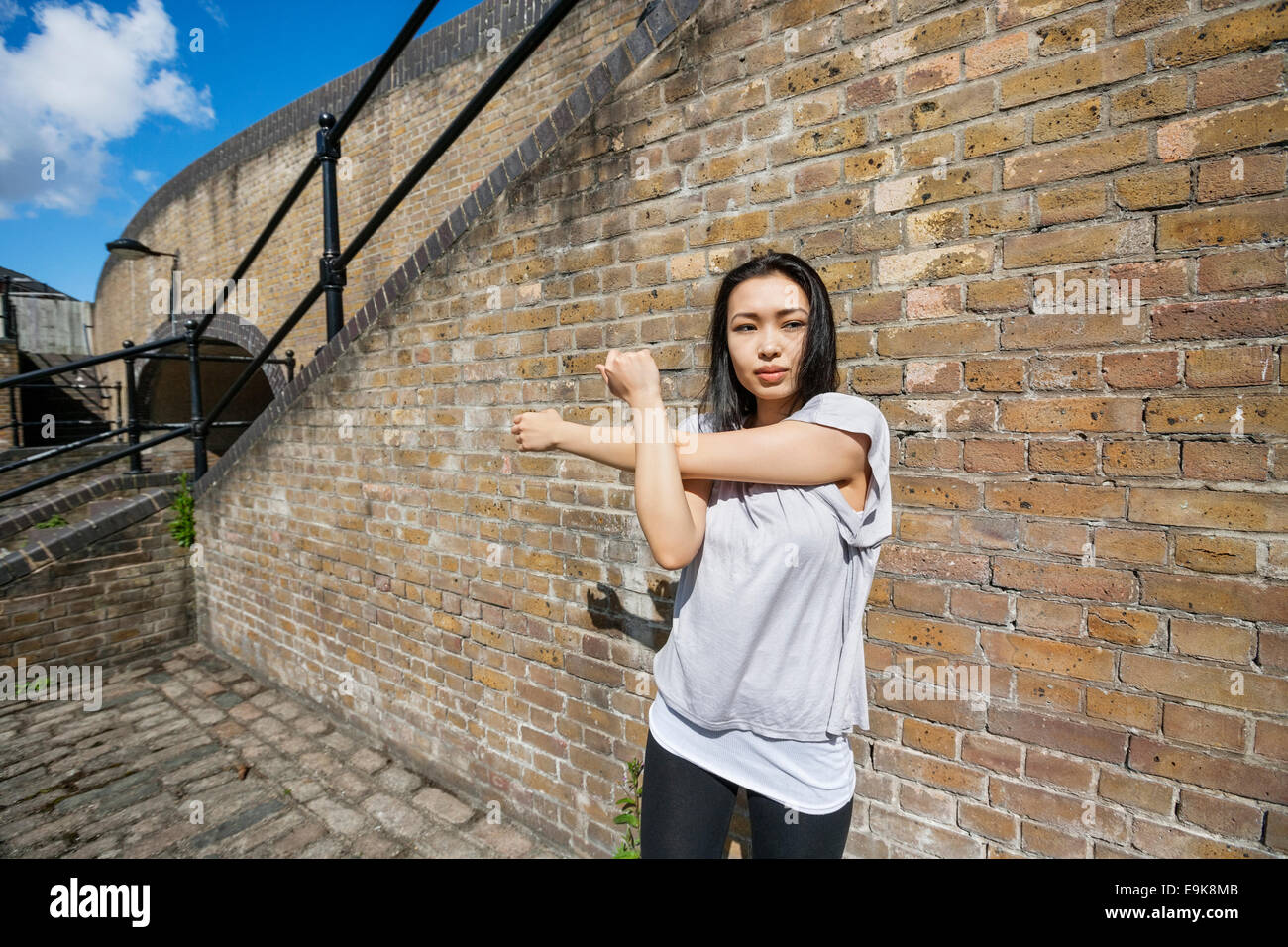 Fit Woman with Ausübung gegen Mauer Stockbild