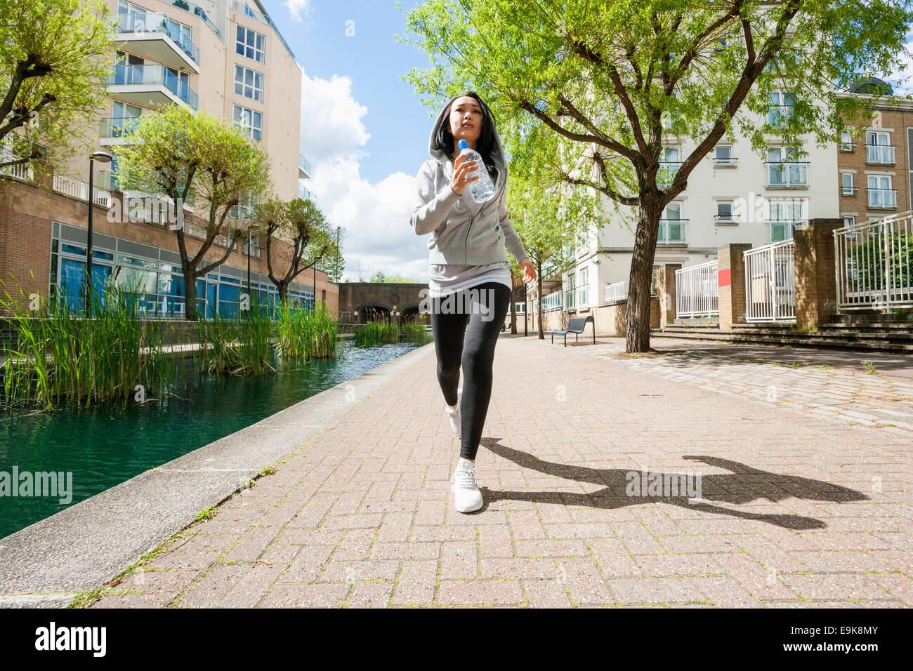 Voller Länge Fit jungen Frau joggen durch Kanal gegen Gebäude Stockbild