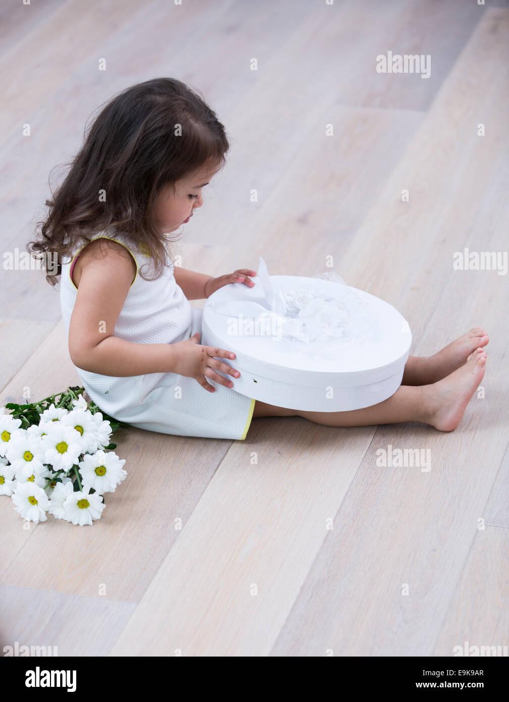 Voller Länge Seite von kleinen Mädchen öffnen Geschenkbox im Stock zu Hause Stockbild