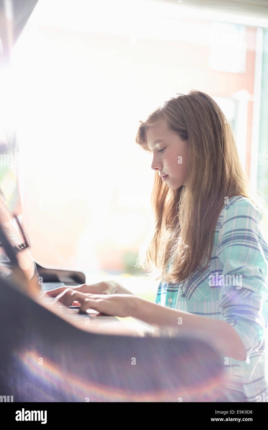 Seitenansicht des Mädchens zu Hause Klavier spielen Stockbild