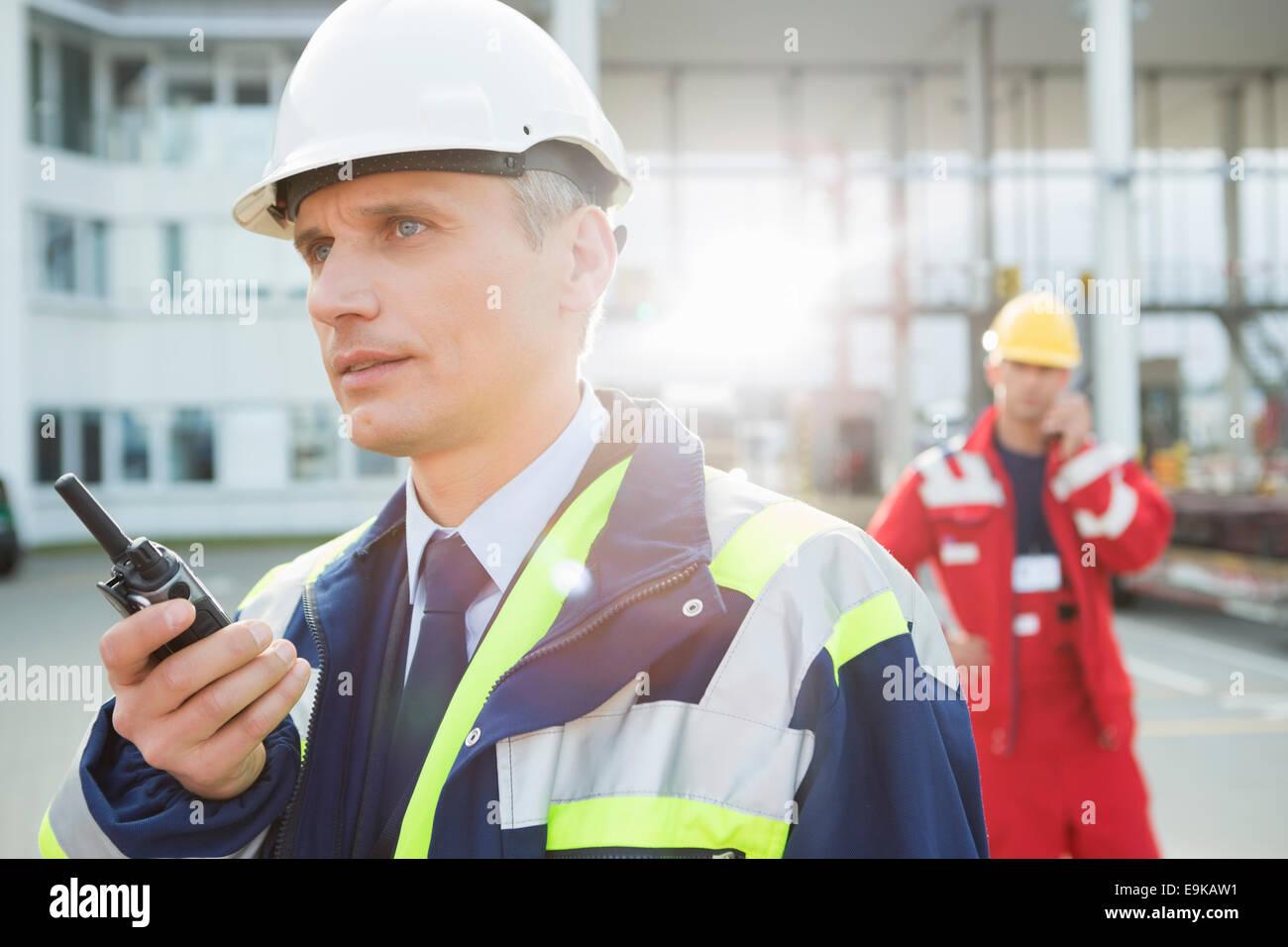 Männliche Arbeiter mit Walkie-talkie mit Kollegen im Hintergrund am Frachthafen Stockbild