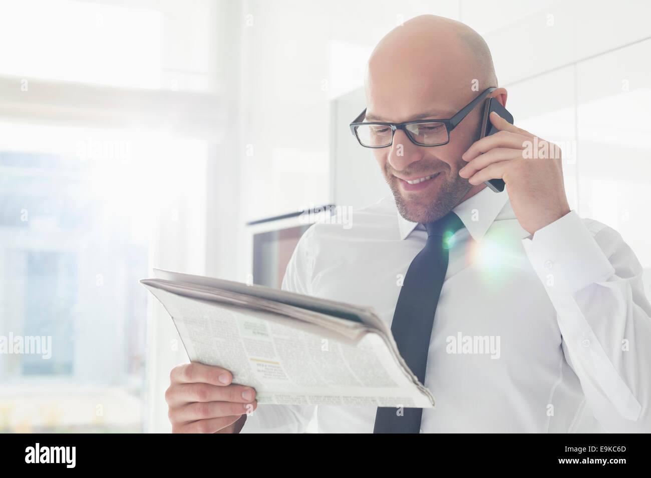 Glücklich Kaufmann auf Abruf beim lesen Zeitung zu Hause Stockbild