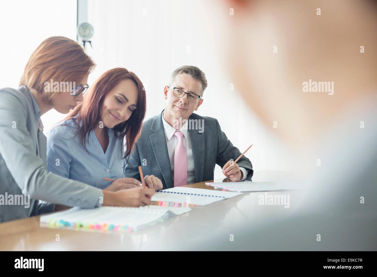 Geschäftsleute, die gemeinsam am Konferenztisch Stockbild