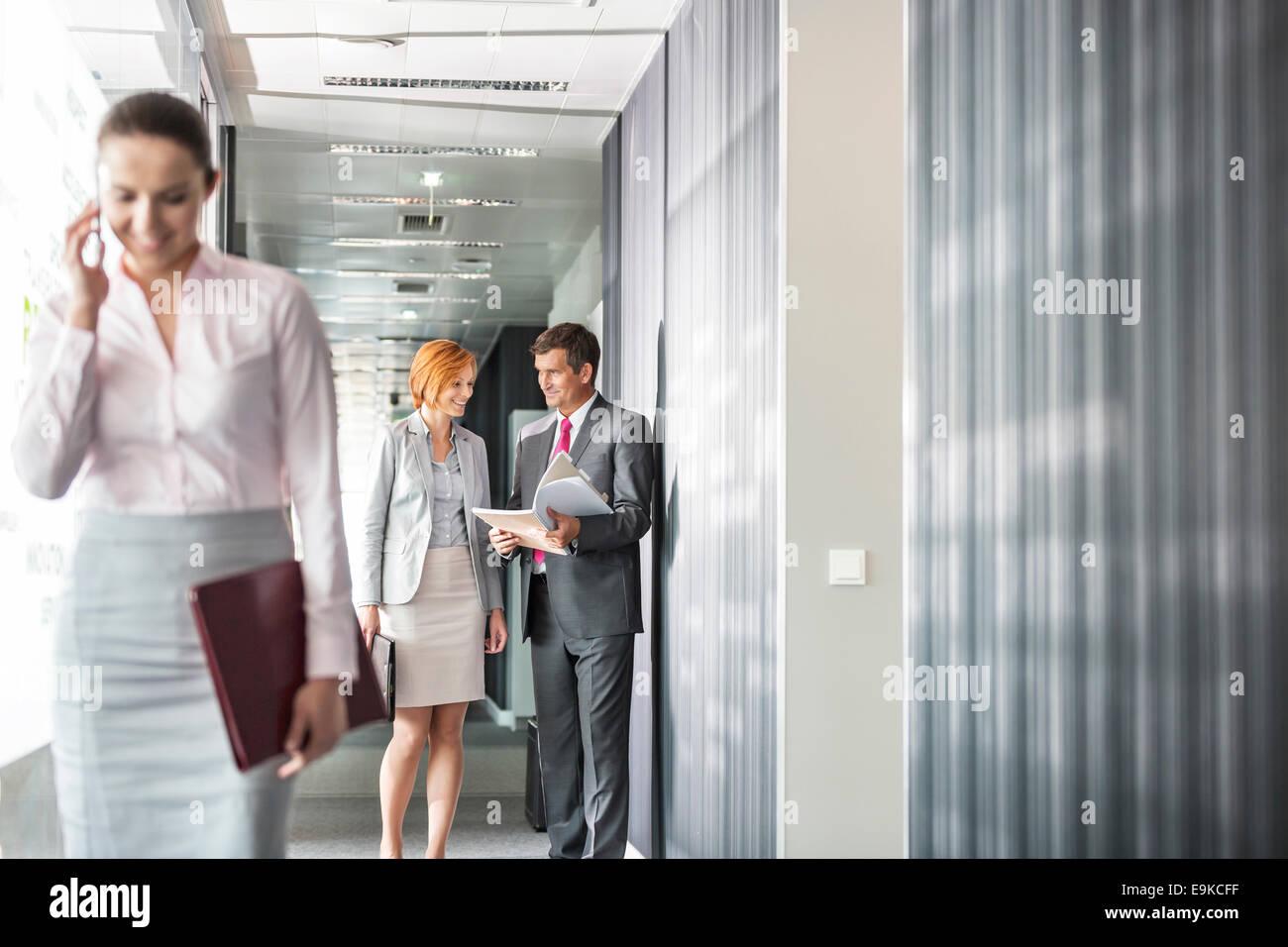 Geschäftsleute, die Diskussion in Gang mit Kollegen mit Handy im Vordergrund Stockbild