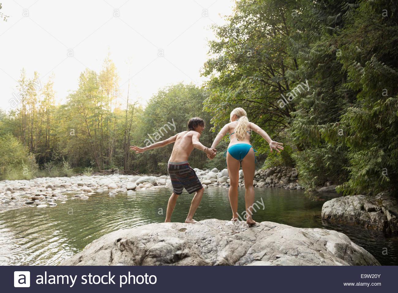 Paar Hand in Hand und springen von Felsen Stockbild