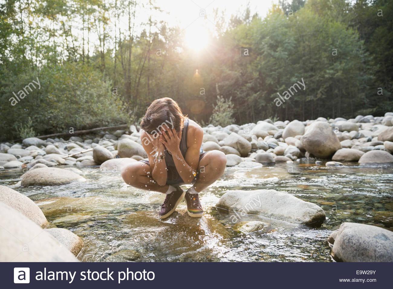 Teenager Spritzwasser auf Gesicht in Bach Stockbild