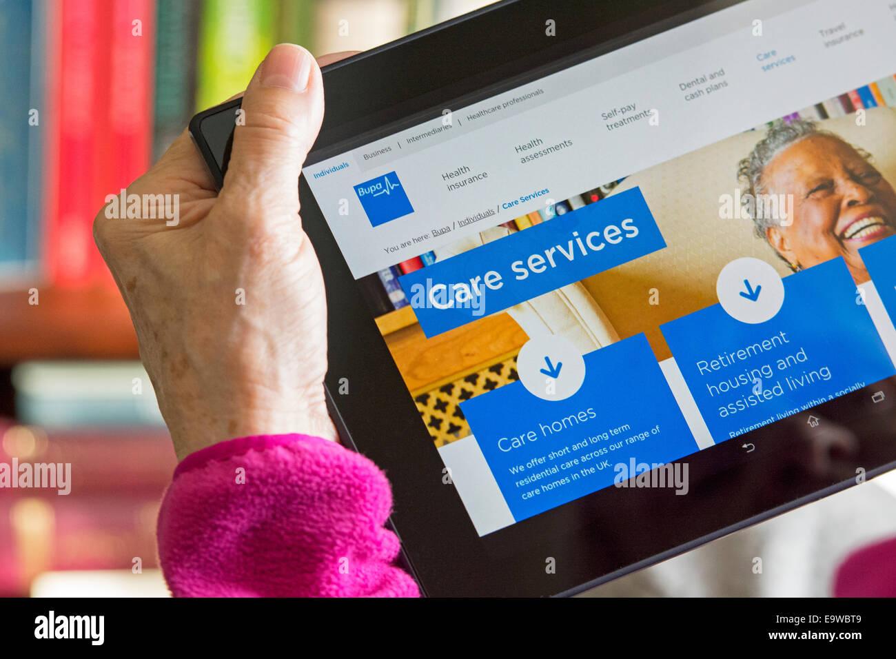 Pflegeheim, Care Services Bildschirm auf Website von Bupa, Frau liest Browsing Web Site für alten-und Pflegeheime Stockbild