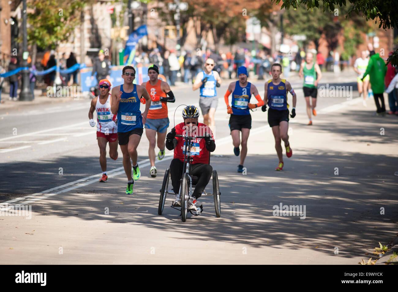 Läufer, einschließlich einen Rollstuhl Teilnehmer durchlaufen Harlem in New York City Marathon Stockbild