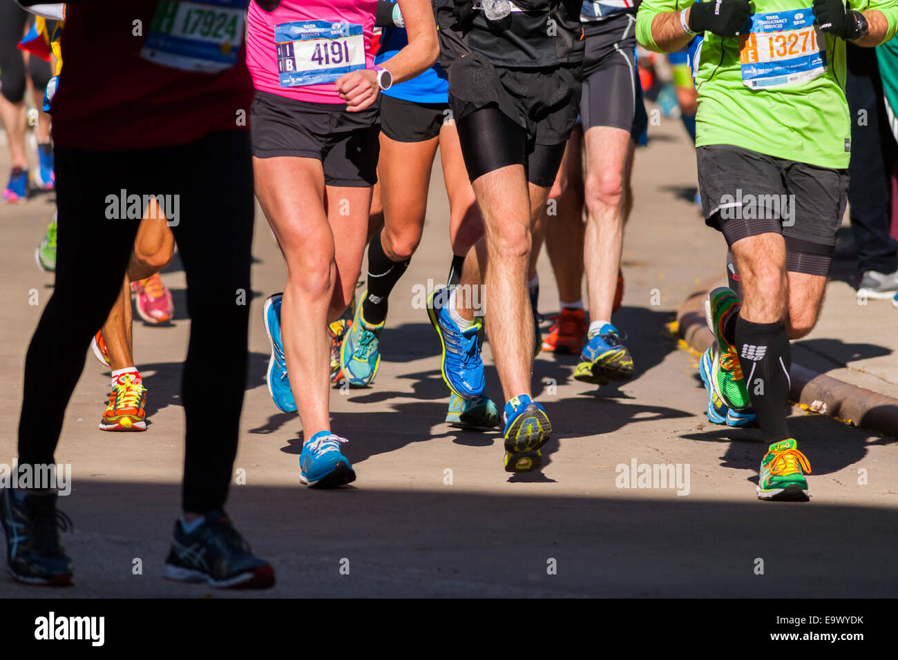 Läufer tragen modische bunte Turnschuhe als Durchgang durch Harlem in New York-Marathon Stockbild