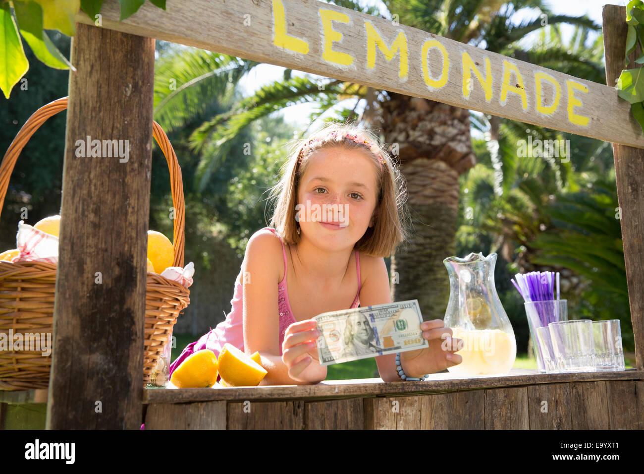 Porträt von Mädchen auf Limonadenstand hält hundert-Dollar-Schein Stockbild