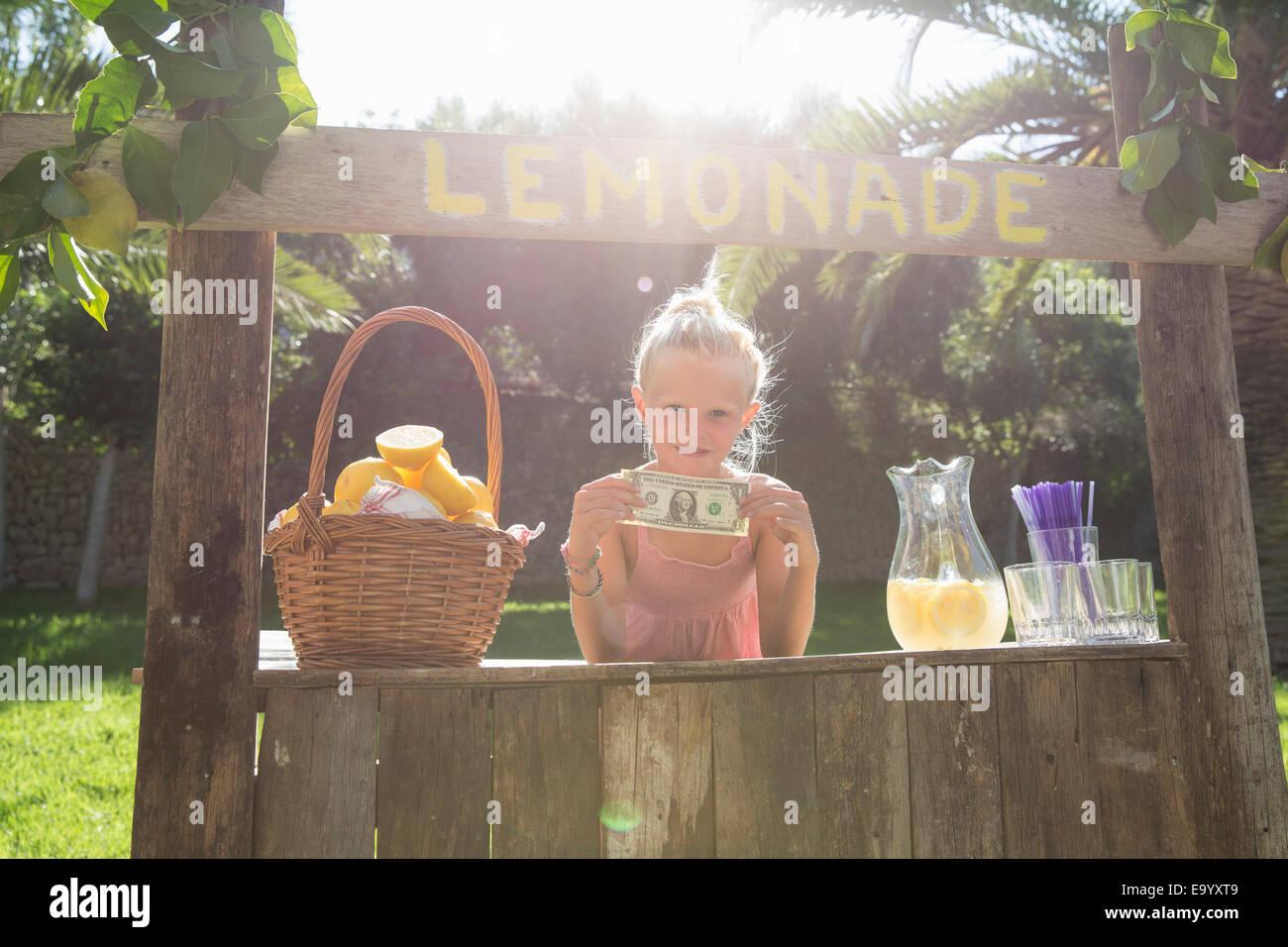 Porträt von Mädchen auf Limonadenstand hochhalten einer Dollarnote Stockbild