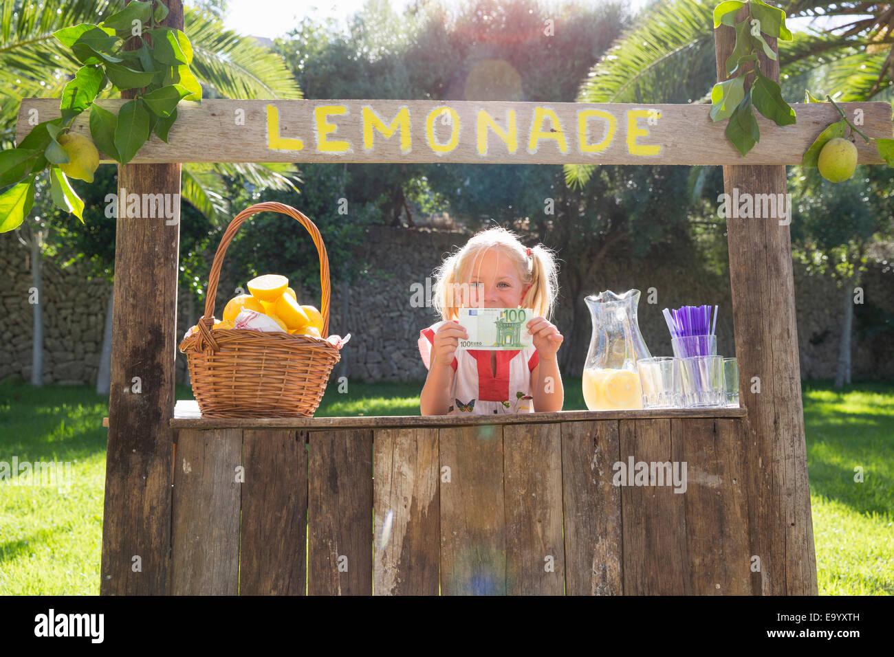 Porträt eines Mädchens auf Limonadenstand hält hundert-Euro-Schein Stockbild