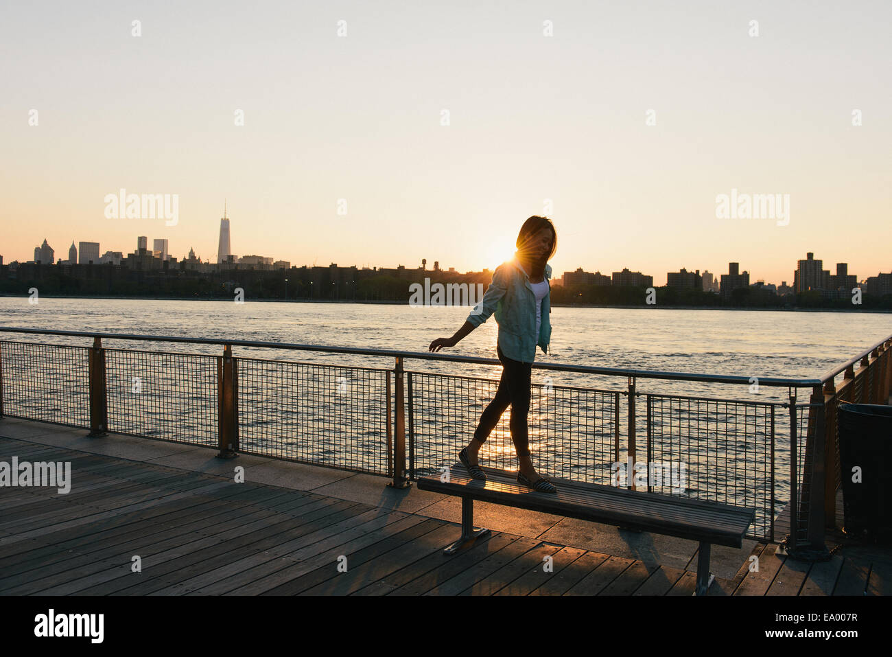 Mitte Erwachsene Frau balancieren auf Bank am Stadt am Wasser bei Sonnenuntergang Stockbild