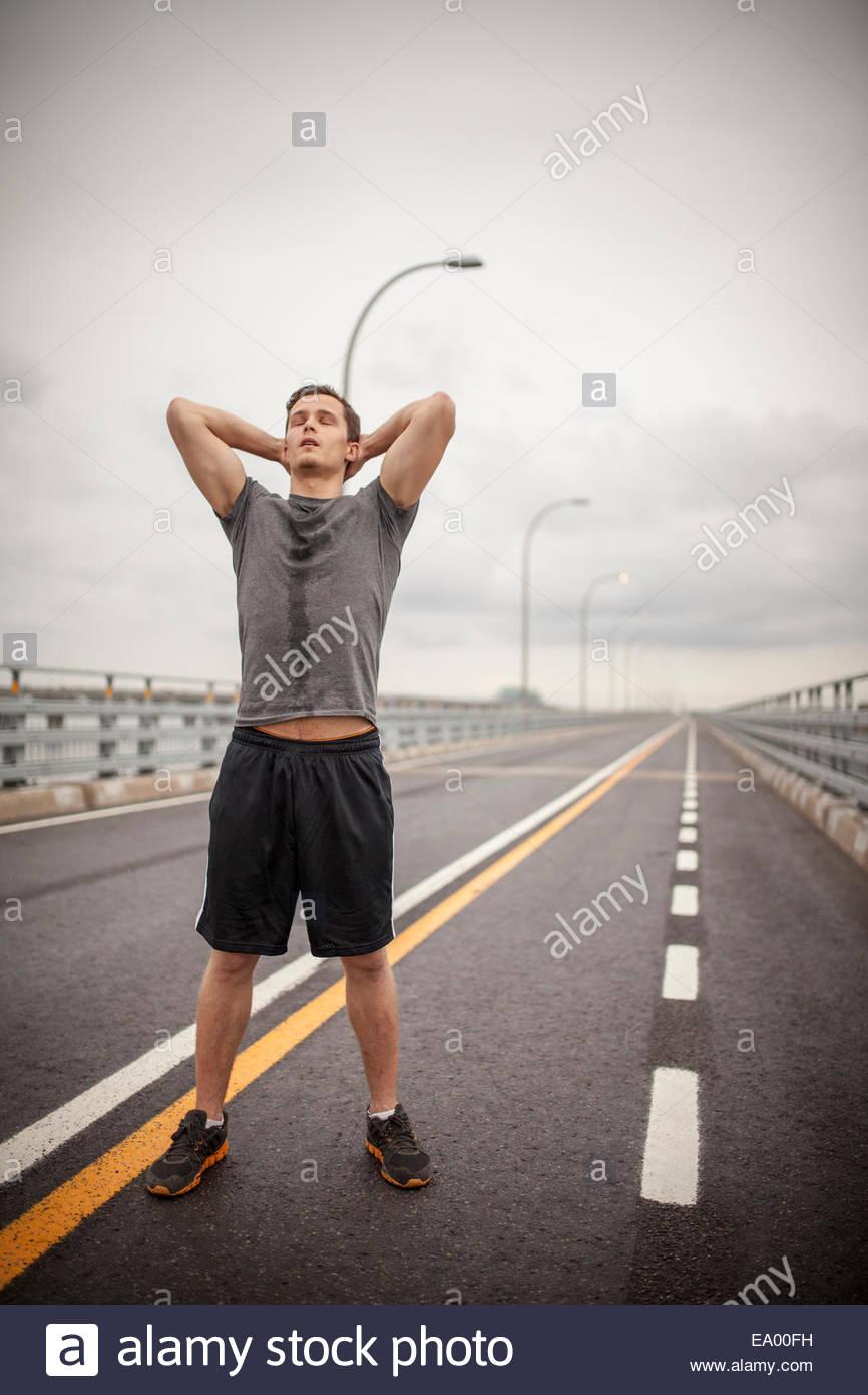 Junger Mann stehend mit Händen hinter dem Kopf Stockbild