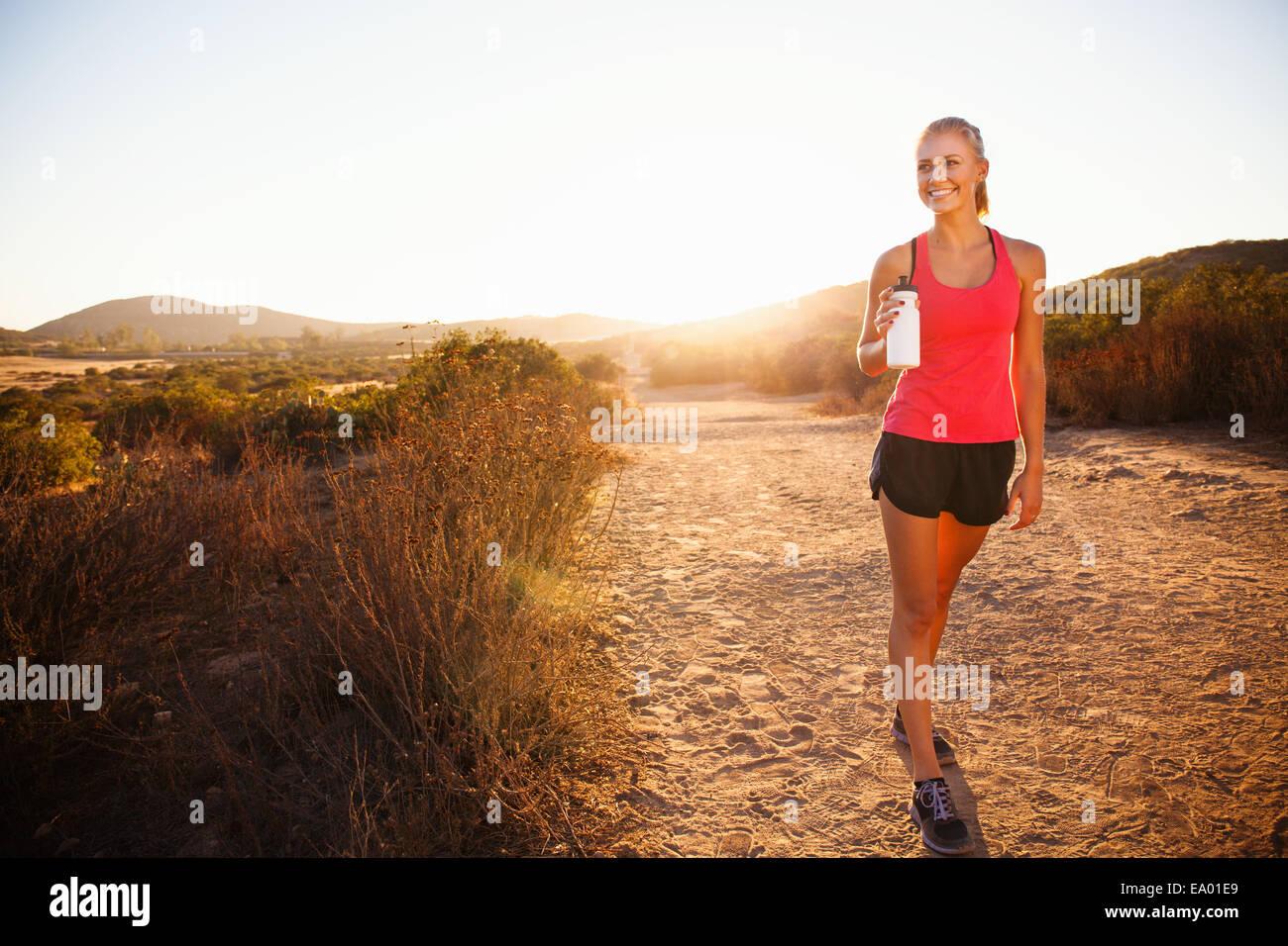 Weibliche Jogger Wasserflasche festhalten Weg, Poway, Kalifornien, USA Stockbild