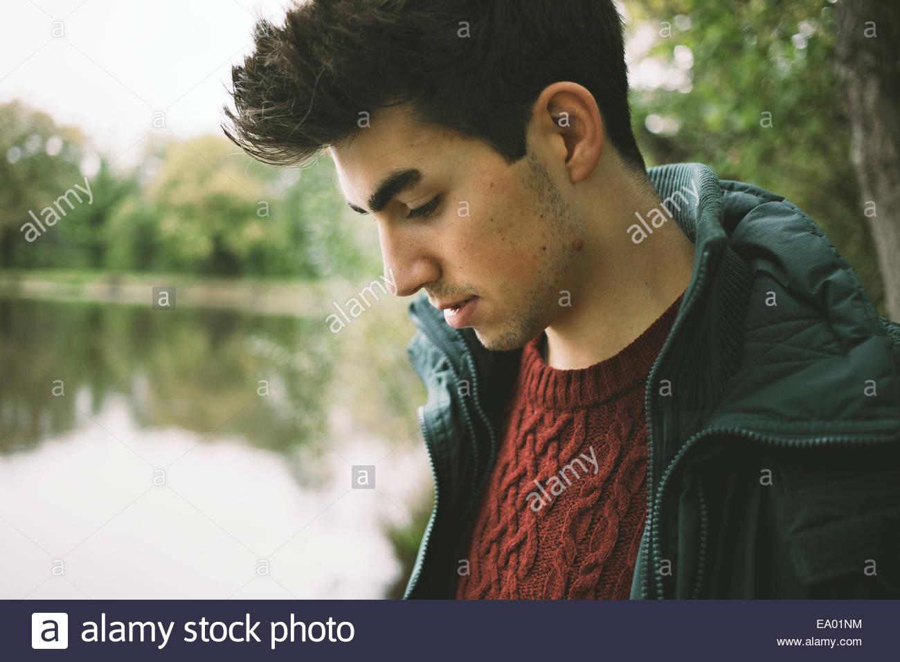 Der junge Mann blickte auf Flussufer hautnah Stockbild