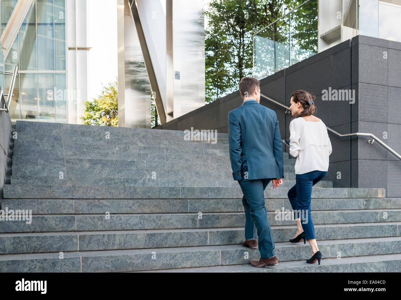Rückansicht des jungen Geschäftsmann und Frau, die Treppe hoch, London, UK Stockbild