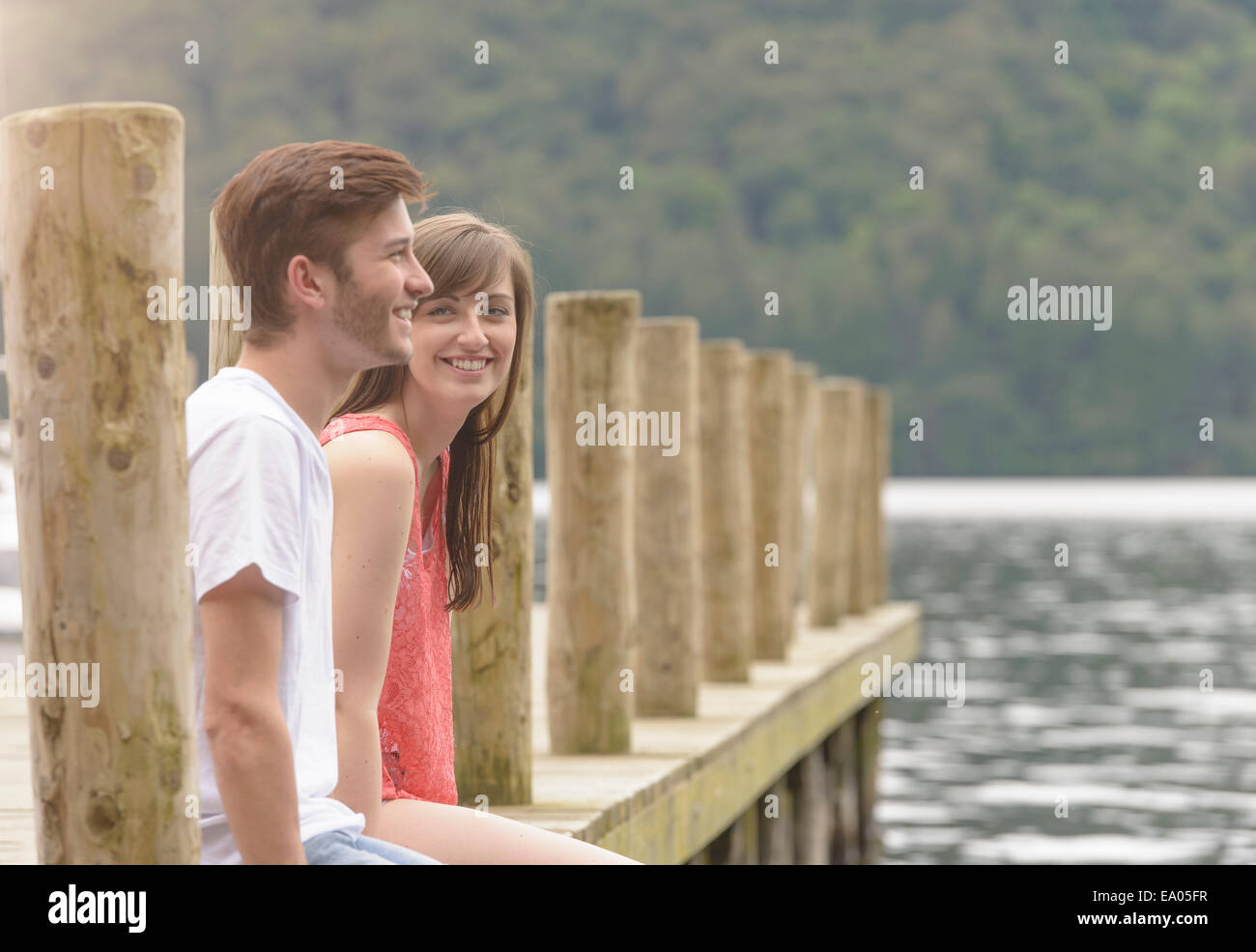 Junges Paar gemeinsam lachen auf Steg über See Stockbild