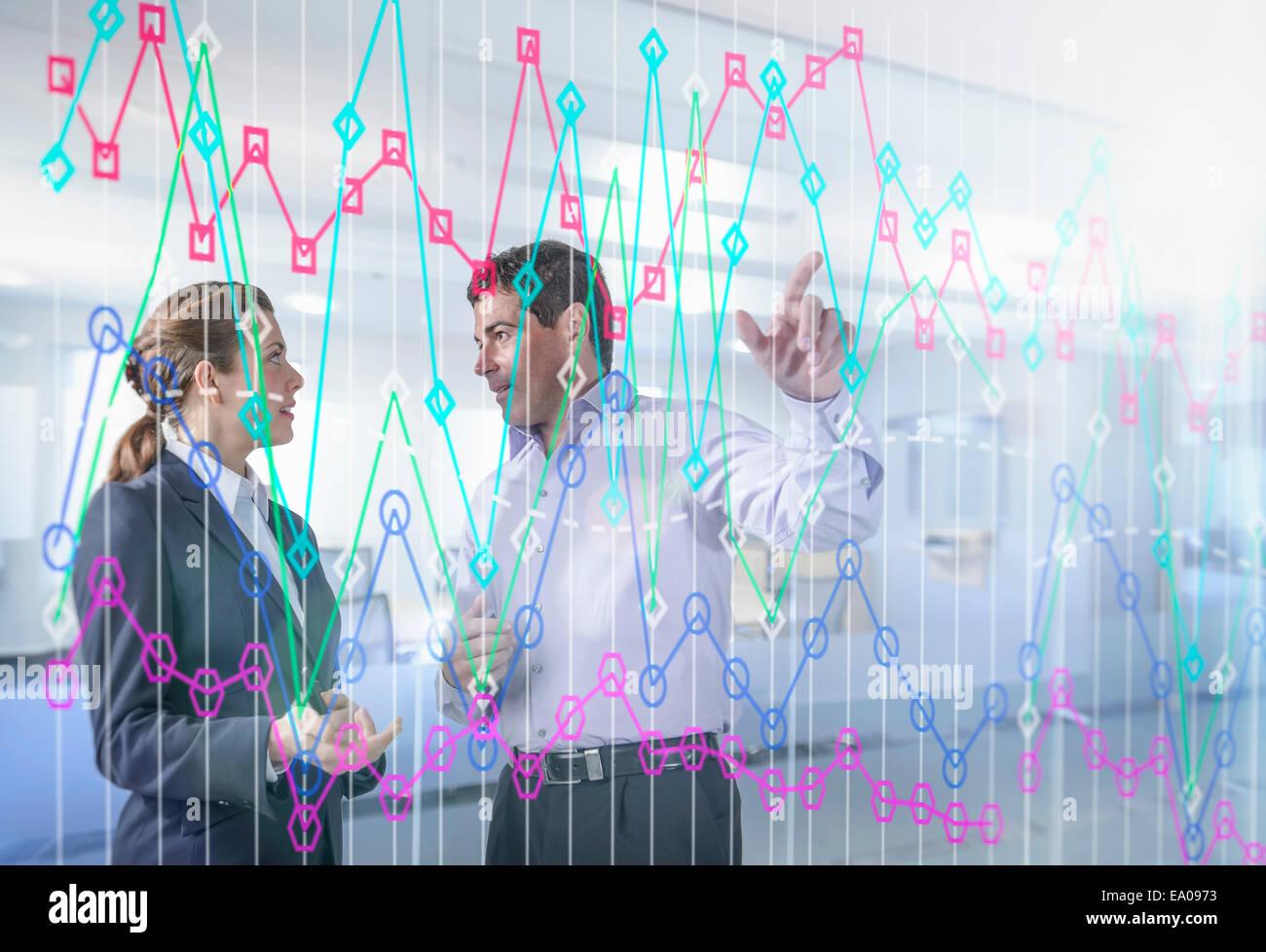 Unternehmer und Unternehmerin diskutieren Graph auf interaktives display Stockbild