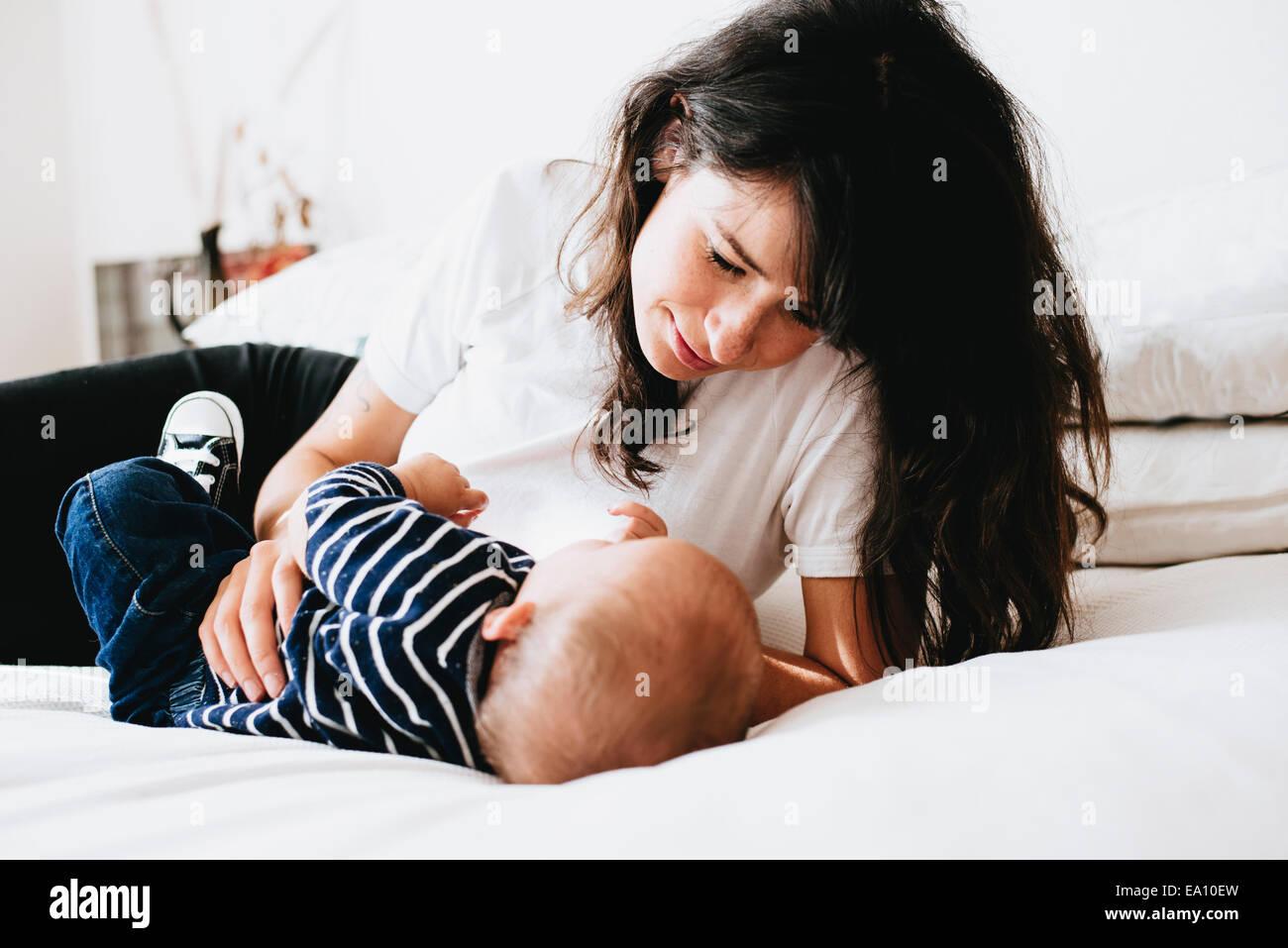 Mutter blickte auf Sohn auf Bett Stockbild