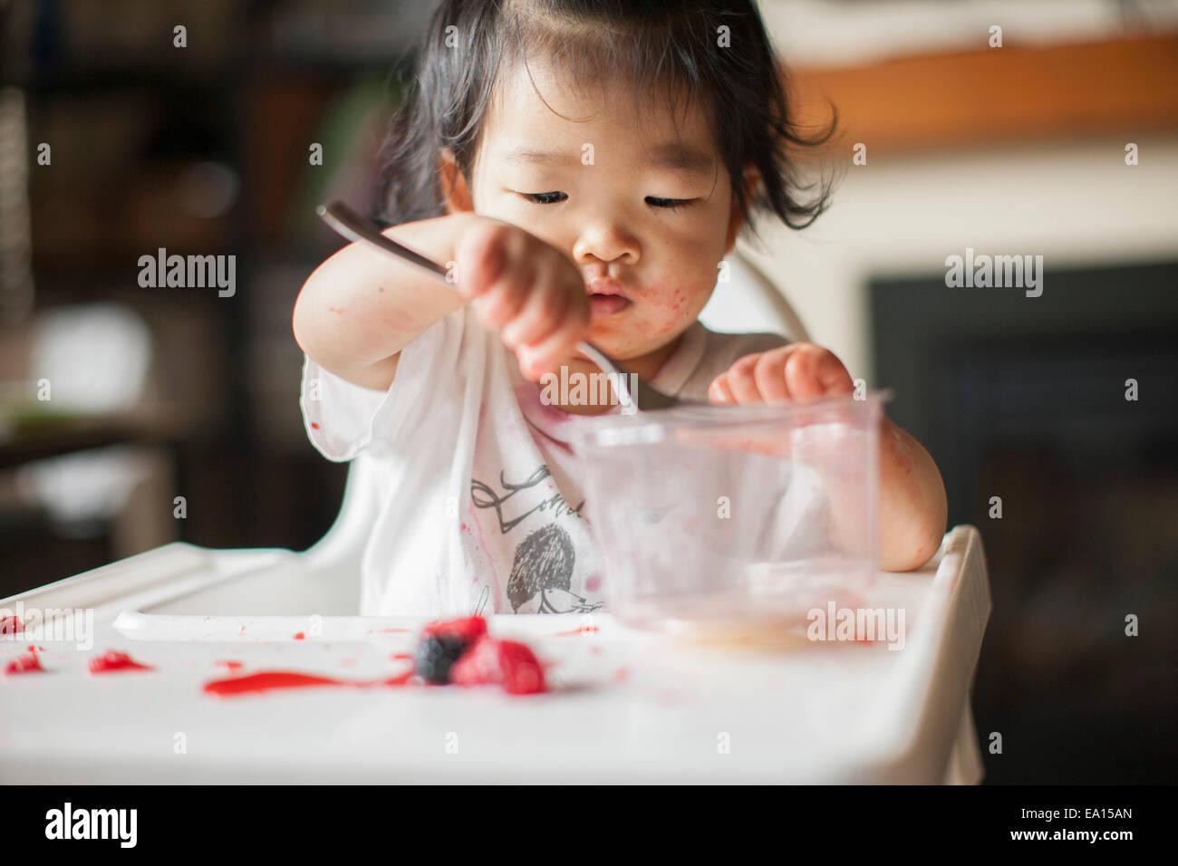 Einjähriges Mädchen essen Obst im Hochstuhl Stockbild